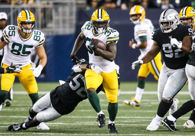 Aug 22, 2019; Winnipeg, Manitoba, CAN; Green Bay Packers running back Tra Carson (32) breaks away from Oakland Raiders middle linebacker Marquel Lee (52) during the third quarter at Investors Group Field.