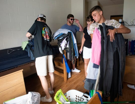 Dawson Proodian, an incoming freshman at the University of West Florida, gets help moving into his new dorm room Friday.