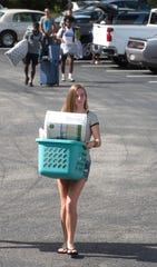 Emily Skyles hauls supplies to the dorms during student move-in day at the University of West Florida on Friday.