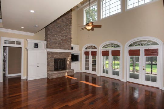 The spacious living area is bathed in natural light and features an elegant fireplace.