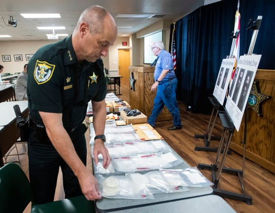 Escambia County Sheriff's Office Chief Deputy Chip Simmons look over evidence on display Friday at the ECSO headquarters during a press conference.