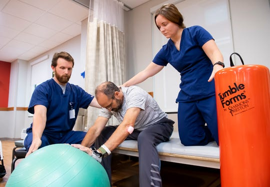 Dave Meixner stretches his back using an exercise ball, as physical therapists Daniel Deitz and Kiley Cruit assist him during a therapy session at Magee Rehabilitation Hospital on Monday, August 19, 2019. His spinal cord injury has left him paralyzed from the chest down. His muscles, like his back muscles, felt tight as he started to exercise on this day.