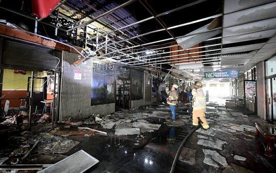 Fire personnel investigate in a common area inside the Yorktown Mall where several business were damaged after an early morning fire Friday, Aug. 23, 2019. The mall is located in the 100 block of North Duke Street. Bill Kalina photo