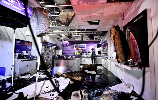 Fire personnel walk through a Metro PCS store inside the Yorktown Mall where several business were damaged after an early morning fire Friday, Aug. 23, 2019. The mall is located in the 100 block of North Duke Street. Bill Kalina photo