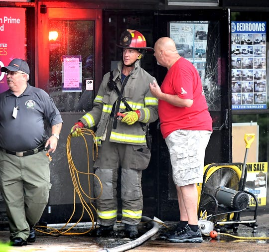 A firefighter speaks with a person outside the Yorktown Mall where several business were damaged after an early morning fire Friday, Aug. 23, 2019. The mall is located in the 100 block of North Duke Street. Bill Kalina photo