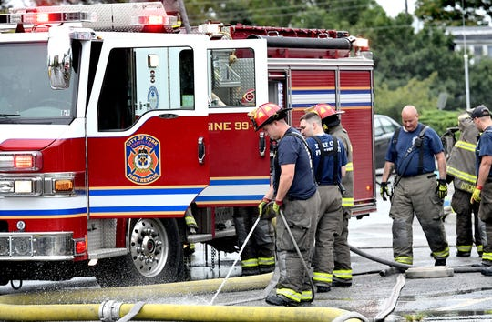 Fire personnel gather equipment outside the Yorktown Mall where several business were damaged after an early morning fire Friday, Aug. 23, 2019. The mall is located in the 100 block of North Duke Street. Bill Kalina photo