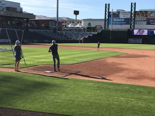Eric Byrnes plays catch with his son and wife  at Greater Nevada Field on Thursday.