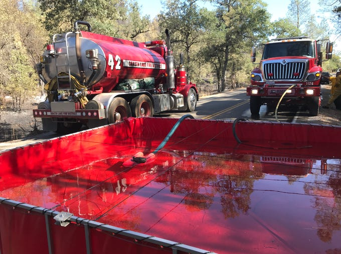 A portable water container sits on Bear Mountain Road northeast of Redding on Friday, Aug. 23, 2019. A water tender delivered the water so a fire engine could send it to a fire hose used to extinguish hot spots in the Mountain Fire.