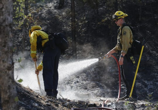 Firefighters from the Marin County Fire Department put out hot spots Friday, Aug. 23, 2019, near a home on Moss Drive in Jones Valley a day after the Mountain Fire burned 600 acres northeast of Redding.