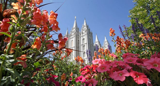 This Aug. 4, 2015 file photo, flowers bloom in front of the Salt Lake Temple, at Temple Square, in Salt Lake City. The Church of Jesus Christ of Latter-day Saints is reminding members that coffee is prohibited no matter how fancy the name, that vaping is banned despite the alluring flavors and that marijuana is outlawed unless prescribed by a competent doctor.