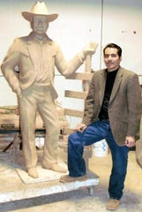 Artist Raul Ruiz stands next to the approved clay model of the Elmer Kelton sculpture, which was cast in bronze and stands in Tom Green County's Stephens Central Library in San Angelo.