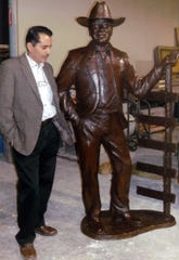 Sculptor Raul Ruiz stands beside the freshly cast bronze statue of author Elmer Kelton he crafted, which now stands in Tom Green County's Stephens Central Library in downtown San Angelo.