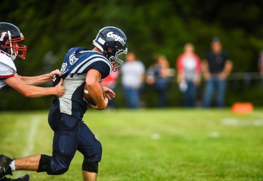 Burke High School fullback and linebacker Finn Hanson (21) runs the ball at Tolstedt field, Friday, Aug. 23.