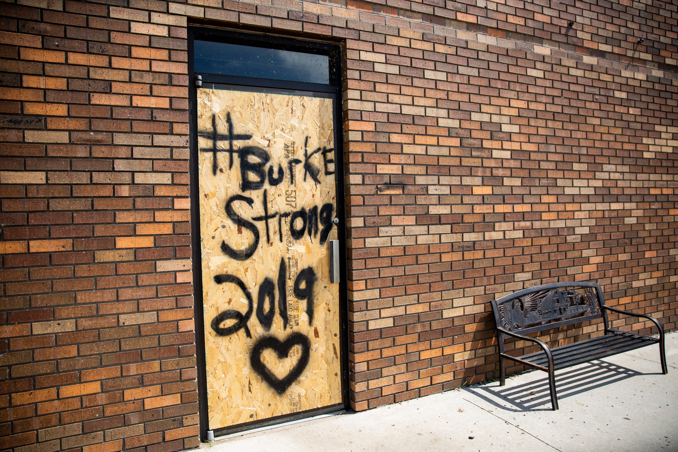 """Burke Strong"" is written on the face of a boarded up doorway in Burke, SD, Friday, Aug. 23."