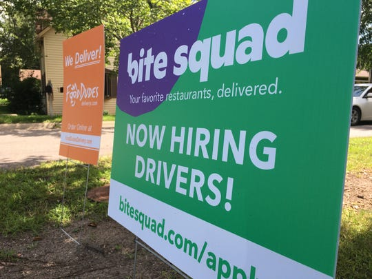 A lawn sign advertising Bite Squad food delivery service shares a grassy patch with a sign for local competitor Food Dudes, Friday, Aug. 23, 2019, near Riverside Park, St. Cloud.