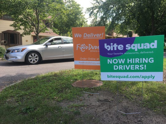 Bite Squad, a Minneapolis-born food delivery service, plans to bring 100 driver jobs to St. Cloud. A sign advertising its services stands near a similar sign for one of its local competitors, Food Dudes, near near Riverside Park in St. Cloud Friday, Aug. 23, 2019. It was Bite Squad's first day of operations in St. Cloud.