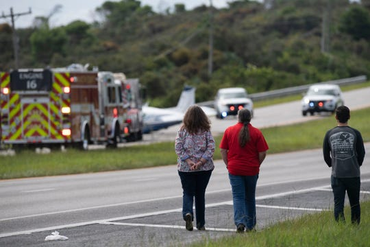 """""""Whoever the pilot was is doggone good. The wires are right there,"""" said Beth Snyder (center), who observed the aftermath of a small plane's emergency landing with her colleagues Karol Kurtz (left) and Jacob Holmes on Friday, Aug. 23, 2019, on U.S. 1 south of Bridge Road near Hobe Sound. The Martin County Sheriff's Office said all three passengers escaped unharmed."""