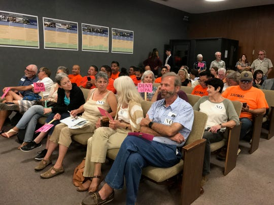 Foes of an apartment and commercial project at Fisherman's Wharf waved pink signs at a hearing Thursday in Oxnard. Construction workers, wearing orange shirts,  supported it.