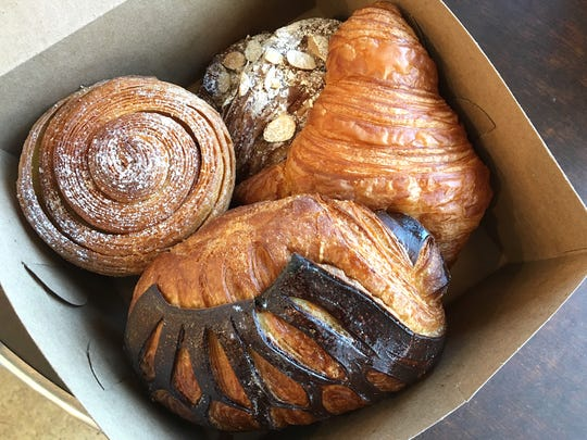 A kouign-amann, left, and almond, plain and chocolate croissants are boxed up for a to-go order at Café Ficelle in Camarillo. The family-owned French-style bakery and cafe also has a location in Ventura.