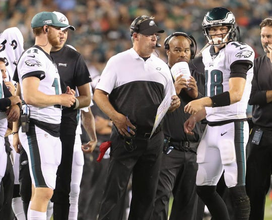 Philadelphia head coach Doug Pederson talks over a two-point PAT attempt with quarterback Josh McCown in the third quarter in preseason action at Lincoln Financial Field Thursday. Eagles starter Carson Wentz, who did not play, watches at left.