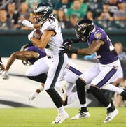 Eagles receiver J.J. Arcega-Whiteside tries to get past Baltimore's Kenny Young (left) and Jimmy Smith in the first quarter in preseason action at Lincoln Financial Field Thursday.