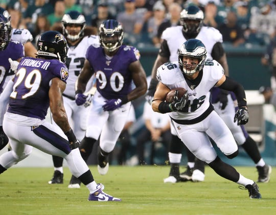 Eagles tight end Zach Ertz (right) carries after a catch as Baltimore's Earl Thomas III moves in during the first quarter in preseason action at Lincoln Financial Field Thursday.