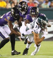 Eagles receiver J.J. Arcega-Whiteside tries to push through Baltimore's (from left) Stanley Jean-Baptiste, Otaro Alaka and Cyrus Jones in the second quarter in preseason action at Lincoln Financial Field Thursday.