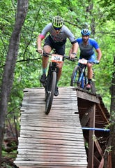 Logan Jenkins, left, and Rick Wetherald ride the elevated Highway to Heaven feature during the Hotter 'N Hell Hundred Off-Road races Friday on the Wee-Chi-Tah Trail.