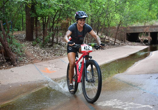 Angie Retzloff of Talequah, Oklahoma grins as she splashes through a water feature while competing in the Hotter 'N Hell Hundred Off-Road races Friday on the Wee-Chi-Tah Trail.