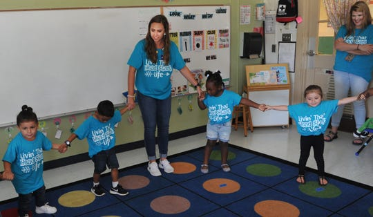 Farris Head Start teacher, Lindsey Duncan and her class of 3-year-old students wear their sponsored Welcome Back to School shirts Friday morning while getting ready for story time.