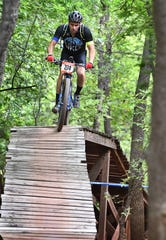 Jason Haislip of Midland, Texas crests an elevated section of the Highway to Heaven bridge during the Hotter 'N Hell Hundred Off-Road races Friday on the Wee-Chi-Tah Trail.