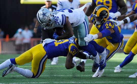 Dallas Cowboys running back Tony Pollard, center, is tackled by Los Angeles Rams defensive back Darious Williams, left, and safety Taylor Rapp during the first half of a preseason NFL football game Saturday, Aug. 17, 2019, in Honolulu. (AP Photo/Mark J. Terrill)