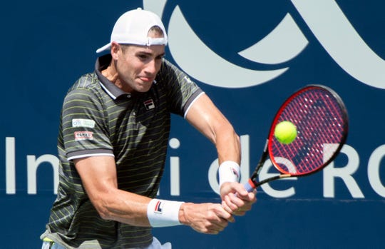John Isner returns to Jordan Thompson of Australia during a first round match at the Rogers Cup.