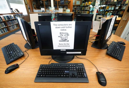 Signs on a bank of computers tell visitors that the machines are not working at the public library in Wilmer, Texas, Thursday, Aug. 22, 2019. Cyberattacks that recently crippled nearly two dozen Texas cities have put other local governments on guard.