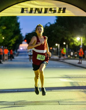 Ronan O'Neill crosses the finish line first in 5 minutes and 4 seconds for the 1 mile run at The Peoples Bank Midnight Flight in Anderson on Friday night August 23, 2019.