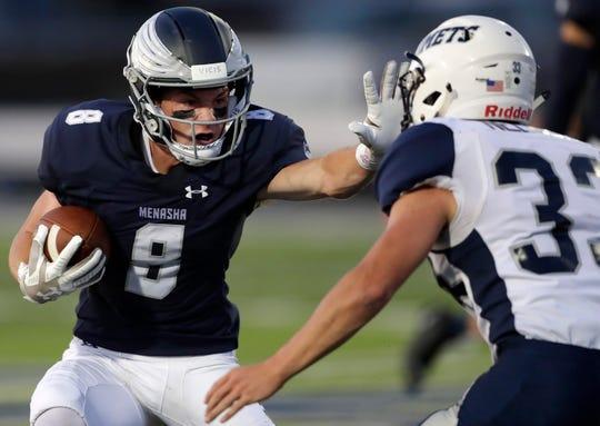 Menasha High School's Brady Jurgella tries to stiff arm Waupaca High School's Wyatt Nelson Friday, Aug. 23, 2019 at Calder Stadium in Menasha, Wis.Danny Damiani/USA TODAY NETWORK-Wisconsin
