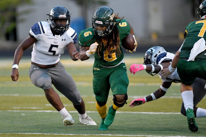 Reynolds' Don Mosely runs the ball against East Forsyth's Torrian Jackson, left, and Jordan Timmons, right, during their season opening game at Reynolds High School on Aug. 23, 2019.