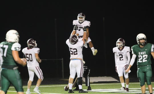 Owen lineman Eli Brasher celebrates a touchdown by Dequan Boyce by lifting his fellow junior in the air.