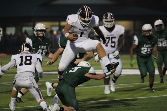 Caleb Scott hurdles an East Henderson defender on his way to a big gain. The junior quarterback rushed for 205 yards on 18 carries in the Aug. 23 season opener.
