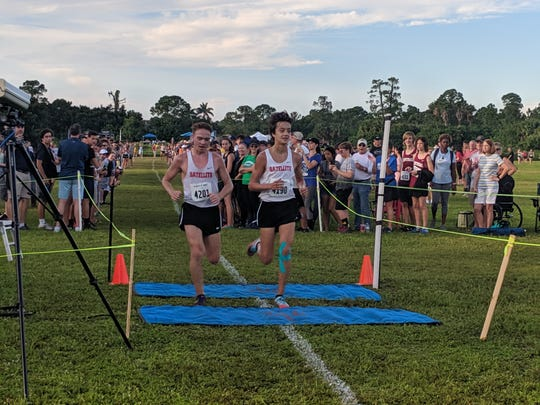 Satellite runners Justin Wilson (left) and Gabe Montague cross the line together at the Fast Feet Invitational. Wilson was the official winner of the boys varsity race.