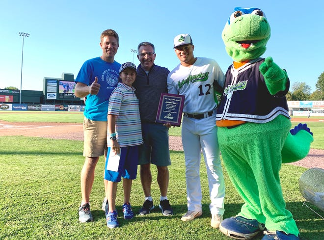 Kyle Bostwick, left, Andrew Fogler and Jim Fogler present Jordan Diaz with the 2019 Tom Racine Award as the Vermont Lake Monsters' MVP at Centennial Field on Saturday night, Aug. 24, 2019.