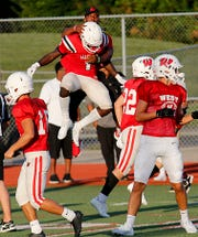 David Afari and coach L.A. Rambsy celebrate after Afari scored a touchdown for Lakota West against Colerain during their scrimmage in West Chester Twp. Friday, August 23, 2019.