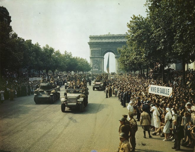 Crowds of French patriots line the Champs-Élysées to view Allied tanks and half tracks pass through the Arc du Triomphe, after Paris was liberated on August 25, 1944.