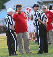Holmes head coach Benjamin K. Nevels talks with referees during the Bulldogs' football game against Boone County, Friday, Aug. 23, 2019.