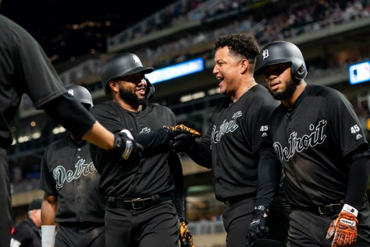 Ronny Rodriguez, left, celebrates his grand slam with Miguel Cabrera, center, in the sixth inning against the Twins at Target Field.