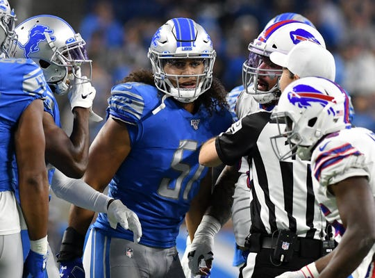 Lions rookie linebacker Jahlani Tavai (51) helps the official separate a couple players in the first half.