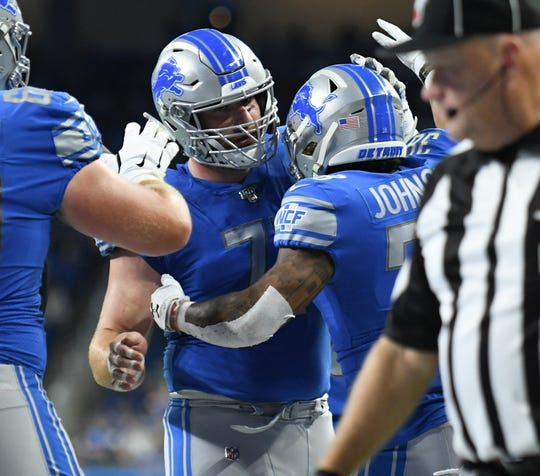 Lions offensive guard Frank Ragnow (77) celebrates with Lions running back Ty Johnson (38) during the preseason.