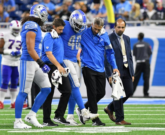 Lions linebacker Jarrad Davis is helped off the field in the first quarter of Friday's preseason game against the Bills.