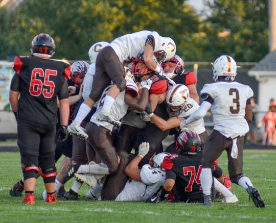 Tough to tackle: Terre Haute South freshman Josh Cottee keeps moving forward despite a host of Evansville Central defenders wrapping him up during Friday's game at South.