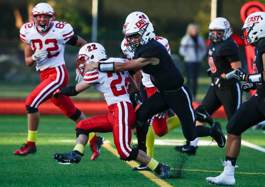 Seymour's Joseph Coonen (22) sprints down the field as a Green Bay East player tackles him during their football game on Friday.